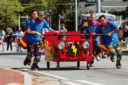 Lawrenceville, GA, USA - April 21, 2018:  A team wearing capes pushes a bed on wheels down a city street in a charity fundraiser event on April 21, 2018 in Lawrenceville, GA. Editorial