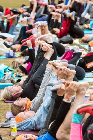 Atlanta, GA, USA - April 8, 2018:  Dozens of people lie on their backs and stretch their legs with a yoga pose as they take part in a massive group yoga class in Piedmont Park on April 8, 2018 in Atlanta, GA.