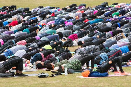 Atlanta, GA, USA - April 8, 2018:  Dozens of people do bridge pose as they take part in a massive group yoga class in Piedmont Park on April 8, 2018 in Atlanta, GA.