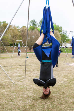 Atlanta, GA, USA - April 8, 2018:  A woman hangs upside down using fabric attached to poles, as she takes part in an aerial yoga class in Piedmont Park on April 8, 2018 in Atlanta, GA. Stock Photo - 117651106