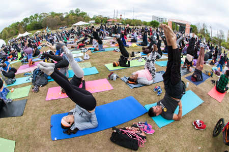 Atlanta, GA, USA - April 8, 2018:  Dozens of people do a yoga pose pointing their toes in the air, as they take part in a massive group yoga class in Piedmont Park on April 8, 2018 in Atlanta, GA. Editorial