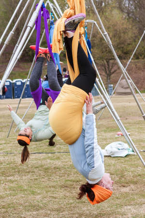 Atlanta, GA, USA - April 8, 2018:  Young women hang upside down using fabric attached to poles, as they take part in an aerial yoga class in Piedmont Park on April 8, 2018 in Atlanta, GA. Editorial