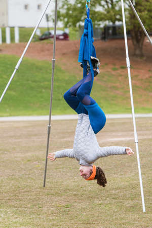 Atlanta, GA, USA - April 8, 2018:  A young woman hangs upside down using fabric attached to poles, as she takes part in an aerial yoga class in Piedmont Park on April 8, 2018 in Atlanta, GA. Editorial