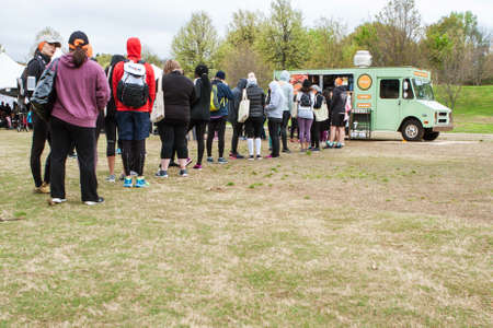Atlanta, GA, USA - April 8, 2018:  People stand in a long line to order from a food truck at an event at Piedmont Park on April 8, 2018 in Atlanta, GA. Editorial