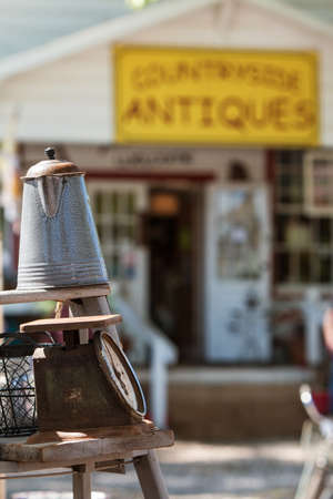 Braselton, GA, USA - April 28, 2018:  Antique coffee pourer and scale are displayed for sale on wooden stepladder outside an antique store at the Braselton Antique Festival on April 28, 2018 in Braselton, GA. Editorial