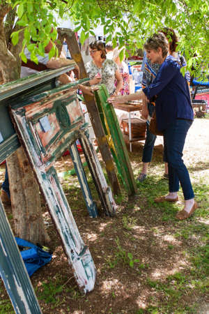 Braselton, GA, USA - April 28, 2018:  A woman looks at an antique wagon wheel and old fireplace mantel pieces on sale at the Braselton Antique Festival on April 28, 2018 in Braselton, GA. Stock Photo - 117651301