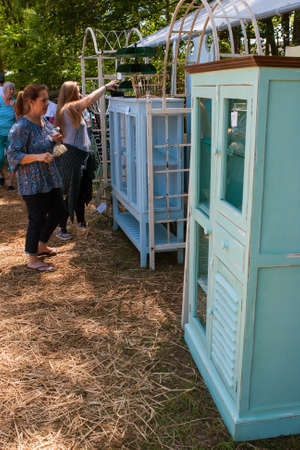 Braselton, GA, USA - April 28, 2018:  Women shop and look at antique cabinets for sale at the Braselton Antique Festival on April 28, 2018 in Braselton, GA. Editorial
