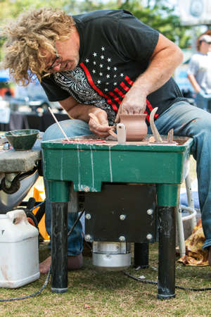 Lawrenceville, GA, USA - April 28, 2018:  A pottery artist forms a bowl with his hands while spinning a pottery wheel as part of a live demonstration at the Lawrenceville Arts Fest on April 28, 2018 in Lawrenceville, GA.
