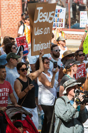 Atlanta, GA, USA - June 30, 2018:  A woman holds a sign saying Jesus was an immigrant at an immigration law protest and march in Atlanta, GA.