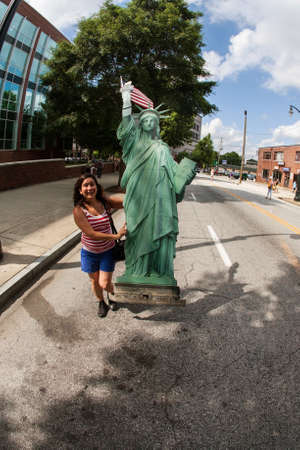 Atlanta, GA, USA - June 30, 2018:  A young woman carries a huge cardboard cutout of the statue of liberty as she hurries to catch up to other marchers at an immigration law protest and march on June 30, 2018 in Atlanta, GA. Redakční
