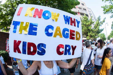 Atlanta, GA, USA - June 30, 2018:  A woman holds a sign saying I know why the caged kids cry at an immigration law protest in Atlanta, GA.