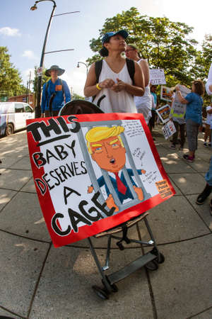Atlanta, GA, USA - June 30, 2018:  A woman transports an anti-Trump sign in a baby stroller, as she and hundreds of people protest immigration laws and Trumps policies at a rally and march on June 30, 2018 in Atlanta, GA.