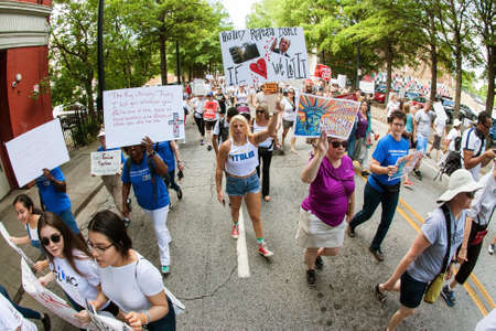Atlanta, GA, USA - June 30, 2018:  People hold anti-ICE and anti-Trump signs and banners as they walk in an immigration law protest and march on June 30, 2018 in Atlanta, GA.
