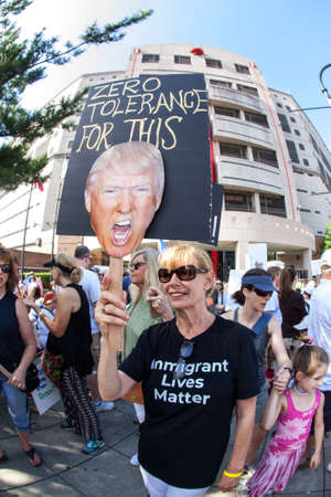 Atlanta, GA, USA - June 30, 2018:  A woman holds a sign saying Zero tolerance for this showing a head shot of Donald Trump, at an immigration law protest in Atlanta, GA.