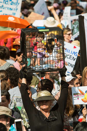 Atlanta, GA, USA - June 30, 2018:  A woman holds up a cage containing doll babies, to protest immigration laws and their impact on immigrant children at a march on June 30, 2018 in Atlanta, GA. Editorial
