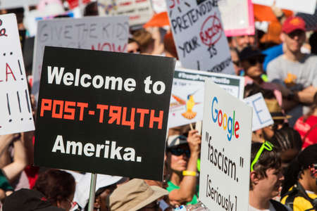 Atlanta, GA, USA - June 30, 2018:  A sign reading Welcome to Post-Truth Amerika stands out among dozens of others at an immigration law protest in Atlanta, GA.