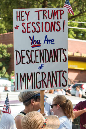 Atlanta, GA, USA - June 30, 2018:  A woman holds a sign saying Hey Trump and Sessions...you are descendants of immigrants at an immigration law protest in Atlanta, GA. Editorial
