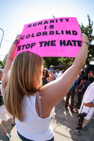 Atlanta, GA, USA - June 30, 2018:  A woman holds a sign saying humanity is colorblind...stop the hate  at an immigration law protest in Atlanta, GA.