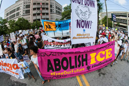 Atlanta, GA, USA - June 30, 2018:  People hold anti-ICE and anti-Trump signs and banners as they line up to take part in an immigration law protest and march on June 30, 2018 in Atlanta, GA.