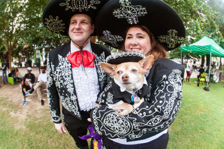 Atlanta, GA, USA - August 18, 2018:  A couple and their chihuahua are dressed in mariachi costumes at Doggy Con, a dog costume contest in Woodruff Park on August 18, 2018 in Atlanta, GA. Stock Photo - 117654345