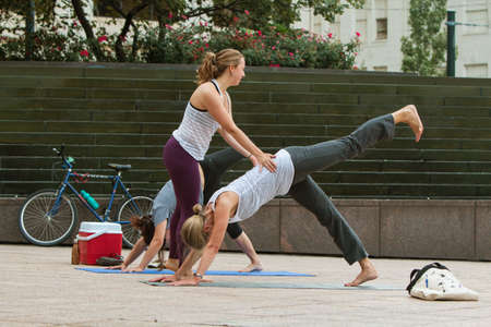 Atlanta, GA, USA - August 18, 2018:  A young female yoga instructor teaches yoga positions to women in a free class at Woodruff Park on August 18, 2018 in Atlanta, GA. Editorial