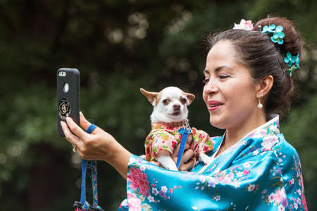Atlanta, GA, USA - August 18, 2018:  A woman wearing a kimono takes a selfie as she holds her small dog, dressed in a kimono costume, at Doggy Con, a dog costume contest in Woodruff Park on August 18, 2018 in Atlanta, GA. Editorial