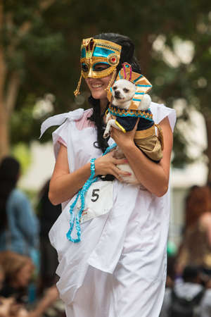 Atlanta, GA, USA - August 18, 2018:  A young woman dressed as an ancient Egyptian carries her small dog dressed as a pharaoh at Doggy Con, an event where dogs and their owners wear costumes and are judged for prizes, on August 18, 2018 in Atlanta, GA. Editorial
