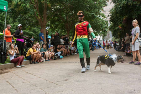 Atlanta, GA, USA - August 18, 2018:  A man wearing a Robin costume walks his dog wearing a Batman costume in front of crowd of spectators at Doggy Con, a dog costume contest in Woodruff Park on August 18, 2018 in Atlanta, GA.