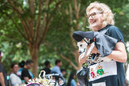 Atlanta, GA, USA - August 18, 2018:  A woman carries a small dog dressed like Darth Vader from Star Wars as she and her dog participate in Doggy Con, a dog costume contest in Woodruff Park on August 18, 2018 in Atlanta, GA.