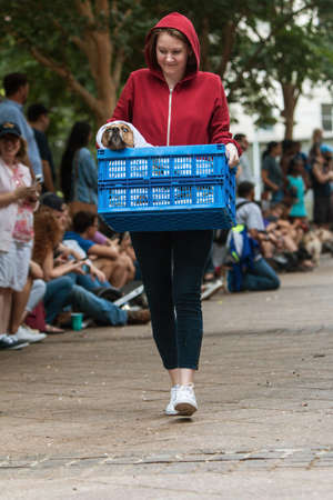 Atlanta, GA, USA - August 18, 2018:  A young woman dressed as Elliott from the movie E.T. carries her dog in a basket, dressed like the extraterrestrial, at Doggy Con, a dog costume contest in Woodruff Park on August 18, 2018 in Atlanta, GA. Editorial