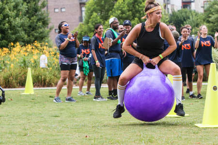 Atlanta, GA, USA - July 14, 2018:  A young woman gets airborne competing in the bouncy ball competition at Atlanta Field Day in the Old Fourth Ward Park, on July 14, 2018 in Atlanta, GA.