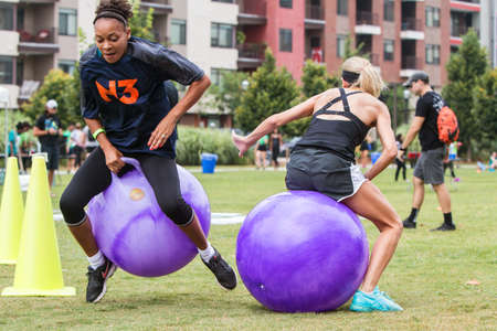 Atlanta, GA, USA - July 14, 2018:  Young women pass each other while racing the course of the bouncy ball competition at Atlanta Field Day in the Old Fourth Ward Park, on July 14, 2018 in Atlanta, GA.