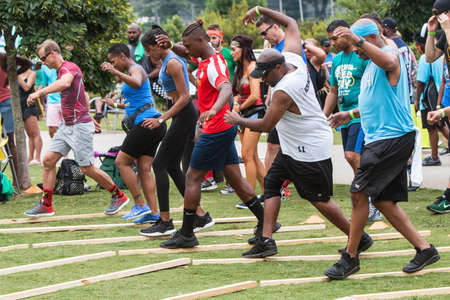 Atlanta, GA, USA - July 14, 2018:  Adult competitors try to maintain their balance while quickly walking over narrow wooden boards in a game at Atlanta Field Day in the Old Fourth Ward Park, on July 14, 2018 in Atlanta, GA. Editorial