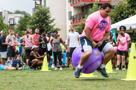 Atlanta, GA, USA - July 14, 2018:  A man gets airborne competing in the bouncy ball competition at Atlanta Field Day in the Old Fourth Ward Park, on July 14, 2018 in Atlanta, GA.