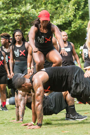 Atlanta, GA, USA - July 14, 2018:  An athletic woman jumps over her male teammates as they compete in the over unders event at Atlanta Field Day in the Old Fourth Ward Park, on July 14, 2018 in Atlanta, GA.