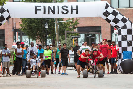 Atlanta, GA, USA - July 14, 2018:  Competitors for two different teams both get a push at the start line as they begin their leg of the adult big wheel relay race at Atlanta Field Day, on July 14, 2018 in Atlanta, GA. Editorial