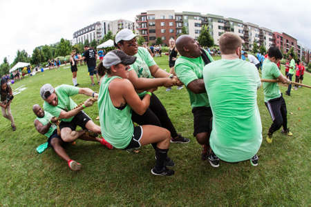 Atlanta, GA, USA - July 14, 2018:  A team of young adult men and women struggle to pull the rope as they compete in a tug of war contest during Atlanta Field Day at Old Fourth Ward Park, on July 14, 2018 in Atlanta, GA.