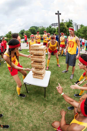Atlanta, GA, USA - July 14, 2018:  A team carefully plays a giant jenga game at Atlanta Field Day in the Old Fourth Ward Park, on July 14, 2018 in Atlanta, GA.