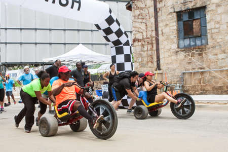 Atlanta, GA, USA - July 14, 2018:  Competitors for two separate teams both get a push at the start line as they begin their leg of the adult big wheel relay race at Atlanta Field Day, on July 14, 2018 in Atlanta, GA.