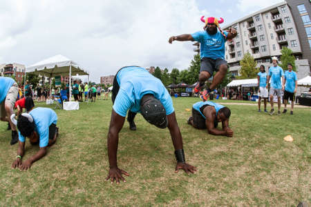 Atlanta, GA, USA - July 14, 2018:  A man gets airborne leaping over a teammate while competing in the over unders event at Atlanta Field Day in the Old Fourth Ward Park, on July 14, 2018 in Atlanta, GA.