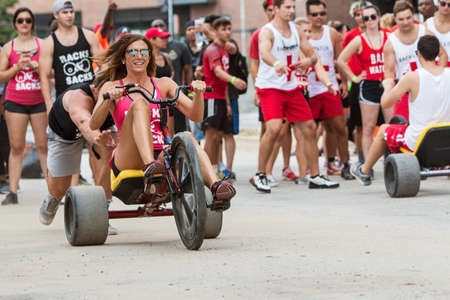 Atlanta, GA, USA - July 14, 2018:  A young woman gets a push at the start line as she begins her leg of the adult big wheel relay race at Atlanta Field Day, on July 14, 2018 in Atlanta, GA. Stock Photo - 117654463
