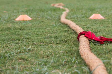 Thick rope with red bandana attached lies on grass before start of tug of war contest