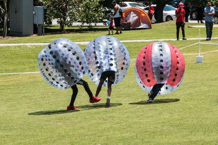 Atlanta, GA, USA - July 28, 2018:  Teenage boys wearing plastic zorbs bump into each other and knock each other down at the Atlanta Ice Cream Festival in Piedmont Park on July 28, 2018 in Atlanta, GA. 報道画像