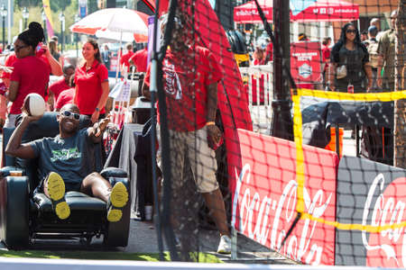 Atlanta, GA, USA - August 25, 2018:  A man sits in a leather recliner, as he attempts to throw a football at a target in a game at the Chick-Fil-A Football Fan Fest to commemorate the start of the college football season on August 25, 2018 in Atlanta, GA. Editorial