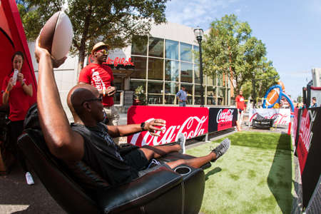 Atlanta, GA, USA - August 25, 2018:  A man prepares to throw a football at a target while sitting in a recliner while participating in a game at the Chick-Fil-A Football Fan Fest on Marietta Street, on August 25, 2018 in Atlanta, GA.