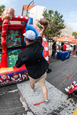 Atlanta, GA, USA - August 25, 2018:  A man throws footballs at targets in an inflatable game at the Chick-Fil-A Football Fan Fest to commemorate the start of the college football season on August 25, 2018 in Atlanta, GA. Editorial