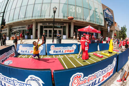 Atlanta, GA, USA - August 25, 2018:  A young boy dives to catch a pass thrown by a volunteer at the Chick-Fil-A Football Fan Fest to commemorate the start of the college football season on August 25, 2018 in Atlanta, GA.