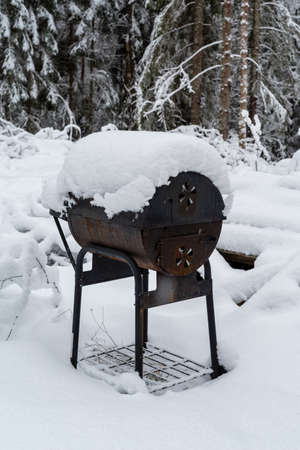 An old bbq grill covered in snow