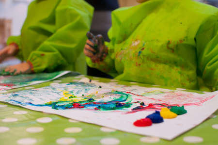 children painting with finger paint