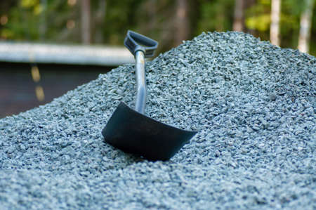 a chovel in a pile of grey gravel infront of a forest Stock Photo